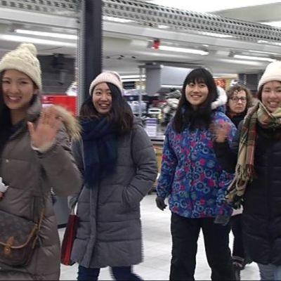 Iloisesti tervehtivä japanilaisryhmä Rovaniemen kauppakeskuksessa.