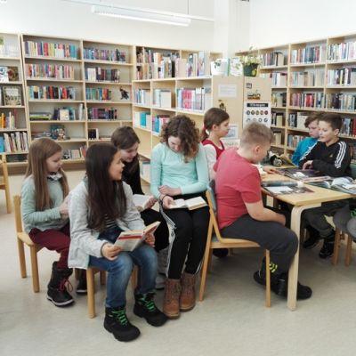 Koululaisia lukemassa Arpelan lähikirjastossa.