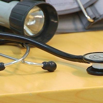Stetoskooppi ja muita sairaalatarvikkeita pöydällä.