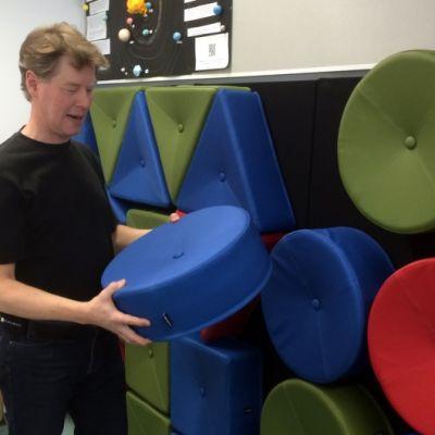 Päämajakoulun rehtori Heikki Väätäinen ja seinällä magneeteilla pysyvät istuinpallit.