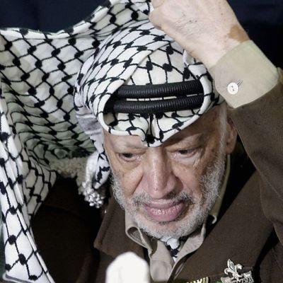 Jasser Arafat asettelee huiviaan 29. heinäkuuta 2004.