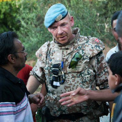 Syyrialaismiehet antavat silminnäkijälausuntoja tanskalaiselle YK-tarkkailijalle Treimsassa, Syyriassa.