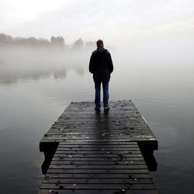 Henkilö seisoo yksin sumuisella laiturilla.