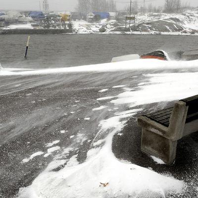 Lumi pöllyää tuulessa Kaivopuiston rannassa Helsingissä.