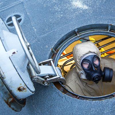 Norjalaisfregatti Helge Ingstadin miehistön jäsen kemiallisten aseiden lastaamista simuloineen harjoituksen aikana Välimerellä.