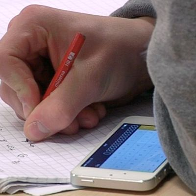 Koululainen kirjoittamassa vihkoon.