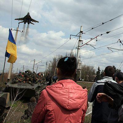Ukrainalaisen panssarikolonnan pysäyttäneet venäläismieliset ihmiset katselevat ukrainalishävittäjän ylilentoa Kramatorskin kaupungin ulkopuolella.