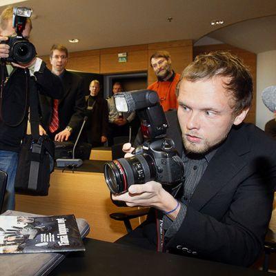 Suomen Kuvalehden valokuvaaja Markus Pentikäinen kuvaa häntä kuvaavaa mediaa Helsingin käräjäoikeudessa.