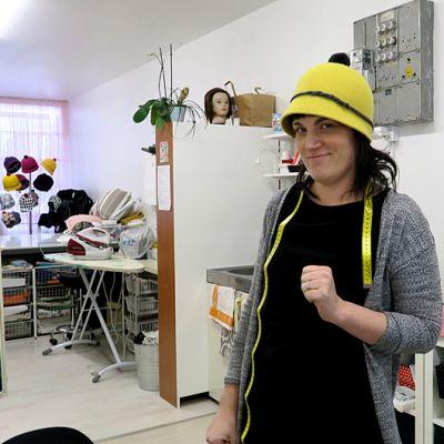 Nainen seisoo myymälässä hattu päässä