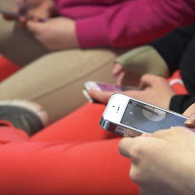Nuoria kännykkä kädessä.