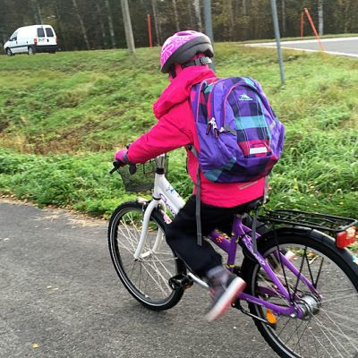 Lapsi pyöräilee kouluun.