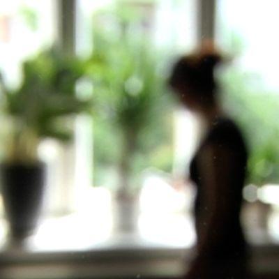 Naisen silhuetti ikkunaa vasten