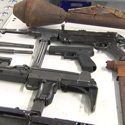 Erilaisia aseita pöydällä.