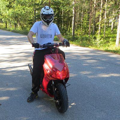 Pietari Partanen skootterinsa kyydissä.
