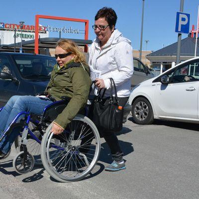 Toimittaja Riikka Rautiainen testaamassa pyörätuolilla Kemin keskustassa liikkumista. Avustajana Teija Suontie.