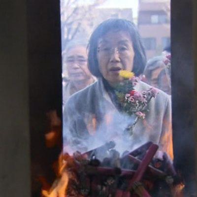 Nainen tuo kukkia Tokion pommitusten uhrien muistomerkille.