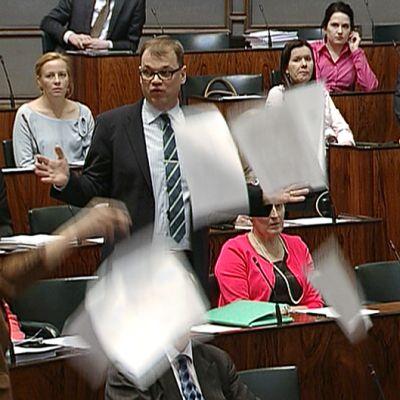 Perussuomalaisten kansanedustaja Veltto Virtanen heittää paperinivaskan ilmaan eduskunnan kyselytunnilla kesken keskustan puheenjohtajan Juha Sipilän puheen.