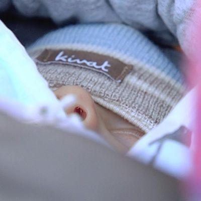 Vauva nukkuu vaunuissa pakkasella.