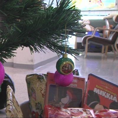 Joulukuusi, kuusen koristeita ja joululahjoja.