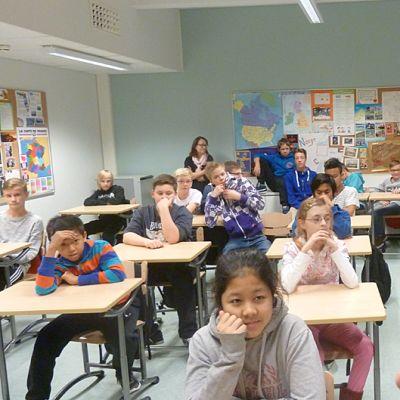 Opettaja esittelee nuorille koululaisille kirjaa.