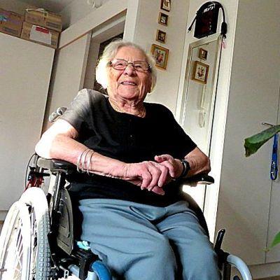 Vanha nainen istuu pyörätuolissa, kun edustalla kukkia.