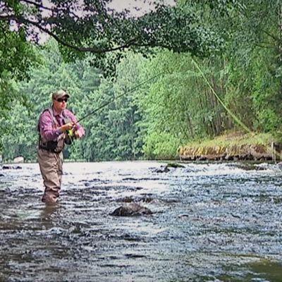 Mies kalastaa koskessa
