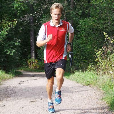 Henkilö juoksee metsätiellä.