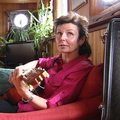 Nainen istuu sohvalla ja soittaa kitaraa.