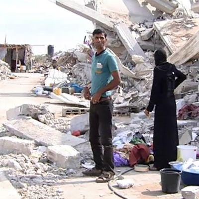 Palestiinalaisperhe tuhotun talon vierellä Gazan kaistalla.