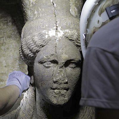 Arkeologit puhdistavat varovasti irtomaasta Pohjois-Kreikasta löytyneen muinaisen haudan naishahmoja.