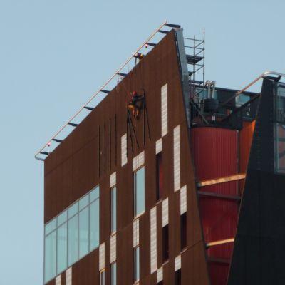 Roman Saukkonen roikkuu valjaissa Tampereen tornihotellin seinällä.