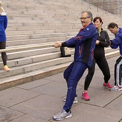 Hallituspuolueiden joukkue valmistautumassa eduskunnan liikuntapäivän avanneeseen köydenvetokilpailuun eduskunnan edustalla.