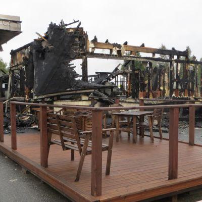Terassi, jonka takana täysin tulipalossa tuhoutuneen Peuran huoltoaseman rauniot.