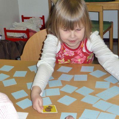 Lapsi pelaa muistipeliä puheterapeutilla.