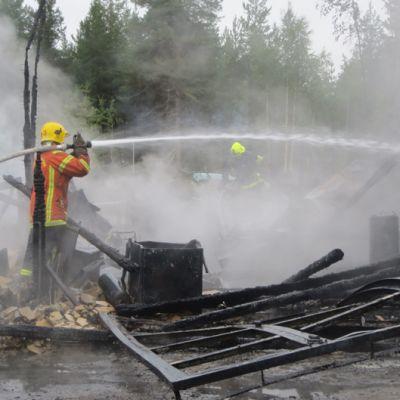 Pelastuslaitoksen palomiehet sammuttamassa Tervolan Peurassa huoltoaseman tulipaloa.