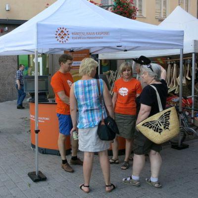 Sibeliuksenkadun ja Reskan risteys Hämeenlinnassa, kaupungin markkinointiteltalla väkeä
