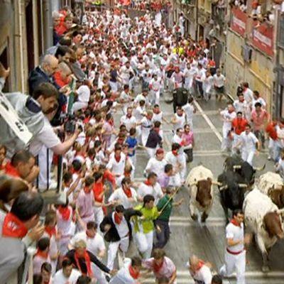 Juoksijoita ja härkiä Pamplonan kadulla.