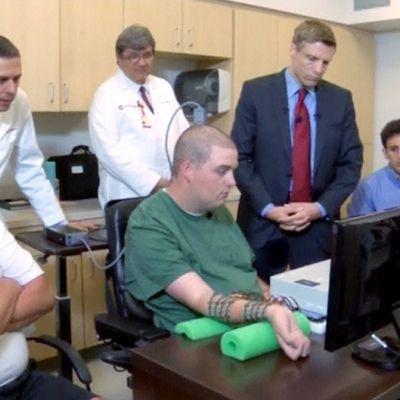 Neliraajahalvaantunut Ian Burkhart, hänen isänsä ja tutkimusryhmän jäsenet testissä, jossa Burkhart liikutti kättään ajatuksensa voimalla.
