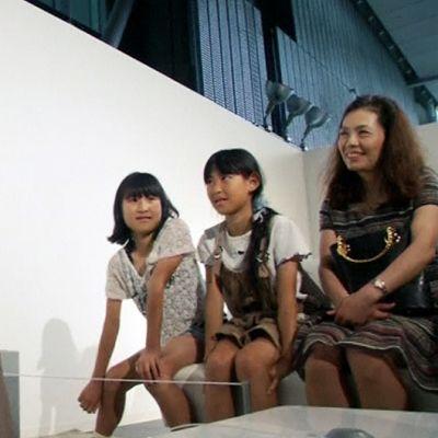 Japanin kansallisen kehittyvän tieteen museon vierailijoita museon näyttelysssä Otonaroid-naisandroidin kanssa.