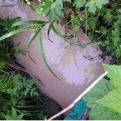 Punertavaa vettä sadevesiojassa