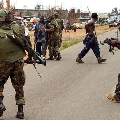 LURD-kapinallisryhmään kuuluva taistelija osoittaa aseella nigerialaisia rauhanturvaajia.
