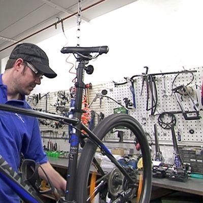 Mies huoltamassa polkupyörää.