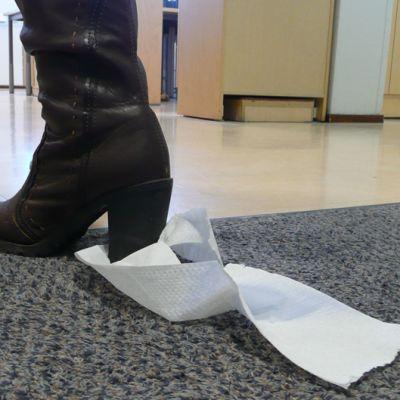 Kengän korkoon on tarttunut vessapaperia.