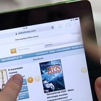 Henkilö selaamassa kirjaston e-kirjasivustoa tabletilla.