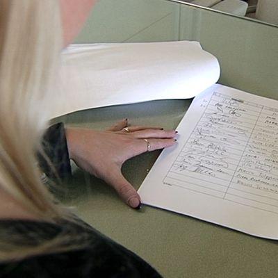 Kansanedustaja Suna Kymäläinen selaamassa maakauppalakialoitteen allekirjoituksia eduskunnassa.