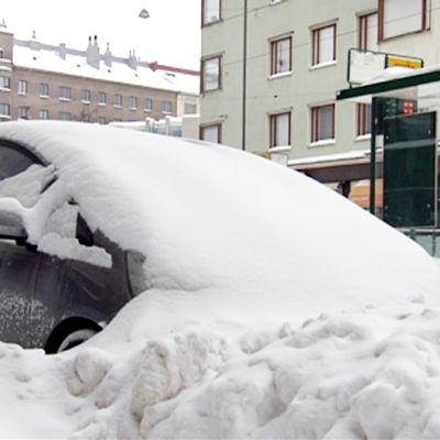 Lumeen peittynyt auto.