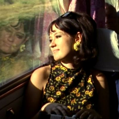 Nainen katsoo maisemaa postiauton ikkunasta