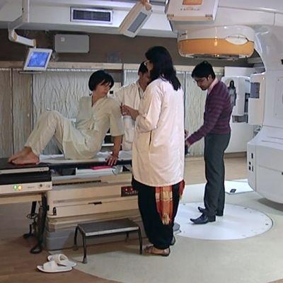 Espoolainen Eija Heinonen valmistautumassa sädehoitoon täsmäsädehoitolaitteessa intialaisessa sairaalassa.