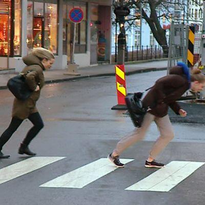 Ihmiset ponnistelevat tuulta vastaan kadulla.