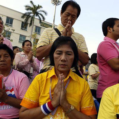 Bangkokin demokratiamonumentin lähistölle kokoontuneet hallitusta vastustavat mielenosoittajat rukoilevat kuninkaan puolesta tämän syntymäpäivänä.